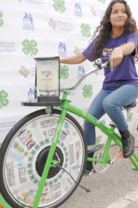 The newspaper feature shows Projecto Juan Diego Heroes-4-Health member Desiree Garcia making an apple smoothie while cycling during Proyecto Juan Diego World Diabetes Day Health Fair